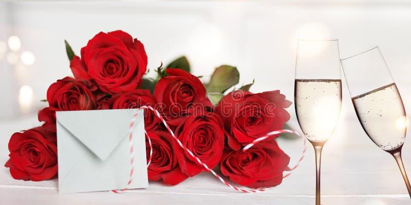 Röda rosor med champagne- och förälskelsebokstaven arkivfoto
