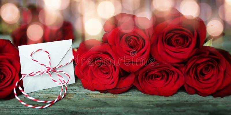 Röda rosor med en förälskelsebokstav fotografering för bildbyråer