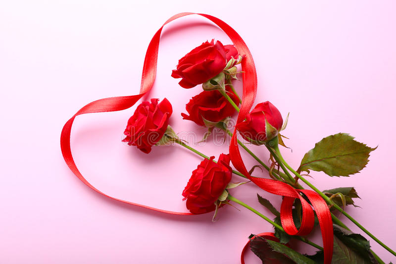 Röda rosor och band arkivbild