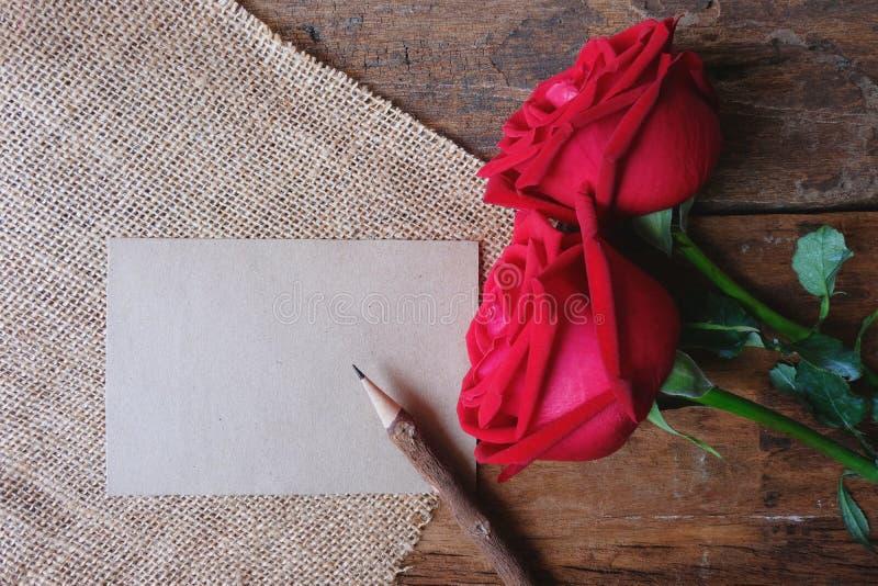 Röda rosor och blyertspenna på trägolvet för Valentine& x27; s-begrepp Pappers- anmärkning för text royaltyfria foton
