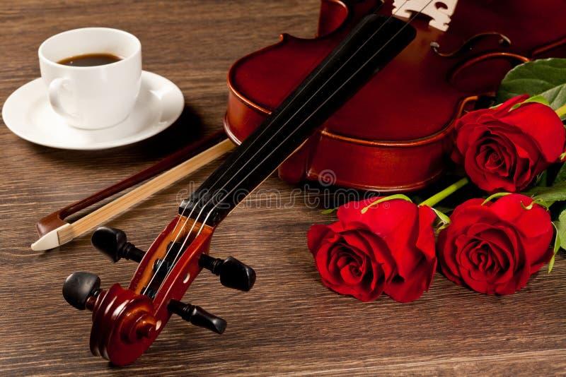 Röda rosor och en fiol arkivbild