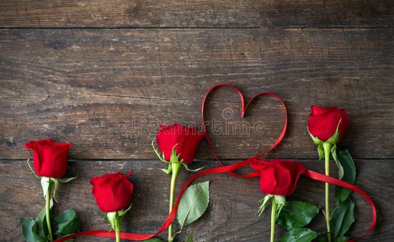 Röda rosor och hjärta formade bandet över trätabellen royaltyfria foton
