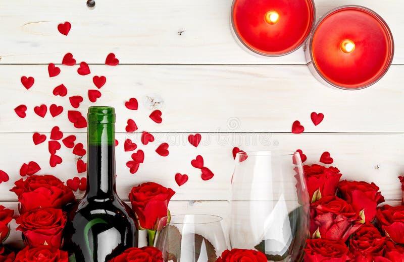 Röda rosor och vin på vit bakgrund arkivbild
