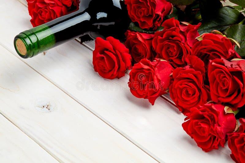 Röda rosor och vin på vit bakgrund royaltyfri bild