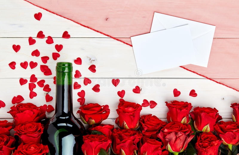 Röda rosor och vin på vit bakgrund royaltyfria foton