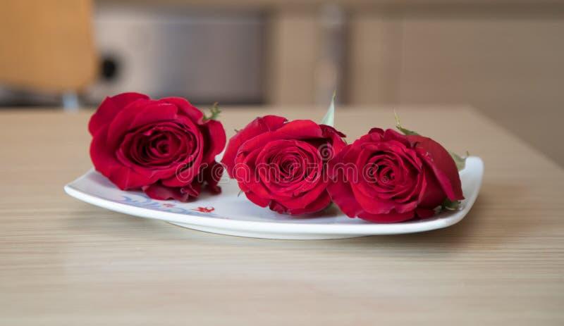 Röda rosor på tabellen arkivbild