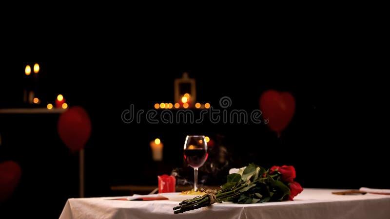 Röda rosor på tabellen nära exponeringsglas av vin, romantisk atmosfär, st-valentindag royaltyfria foton