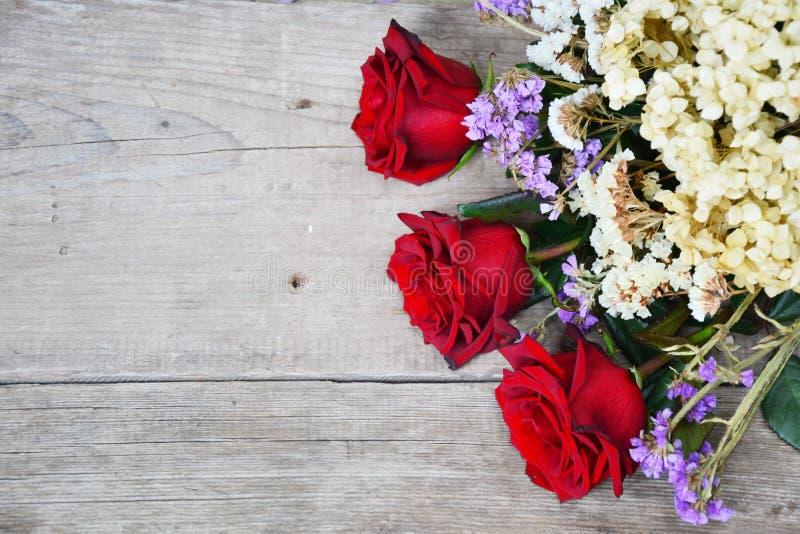 Röda rosor på träbakgrund arkivfoton