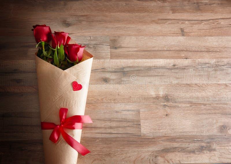 Röda rosor på träbakgrund royaltyfri foto