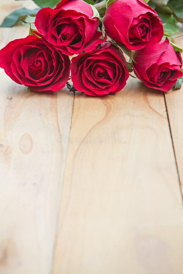 Röda rosor woonden på bakgrund för bakgrundsdagguld röd s valentin för hjärtor royaltyfri fotografi