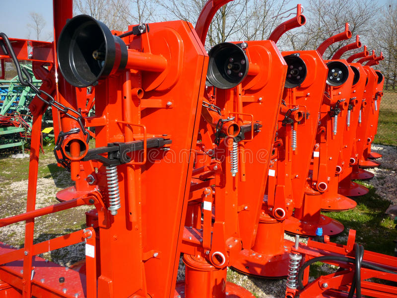 Röda roterande gräsklippningsmaskiner royaltyfria foton