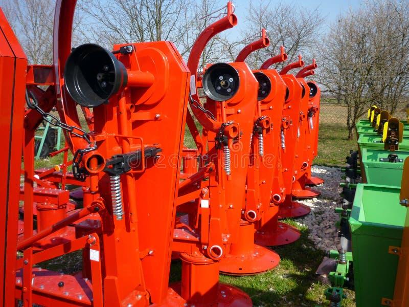 Röda roterande gräsklippningsmaskiner arkivbild
