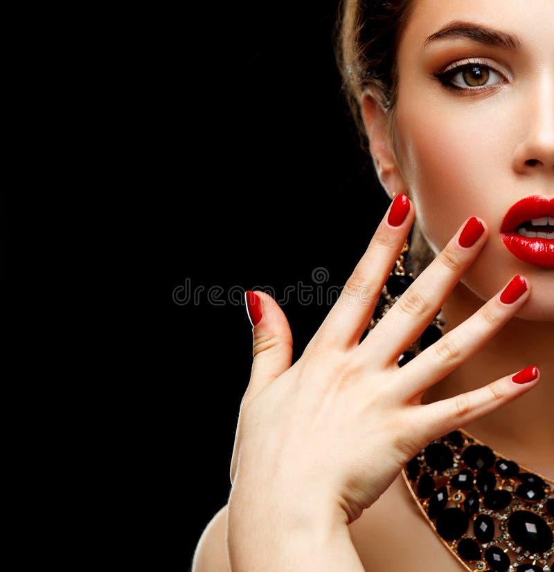 Röda sexiga kanter och spikar closeupen Manikyr och makeup Fyrkantig sammansättning Halva av skönhetmodellflickas framsida på arkivfoto