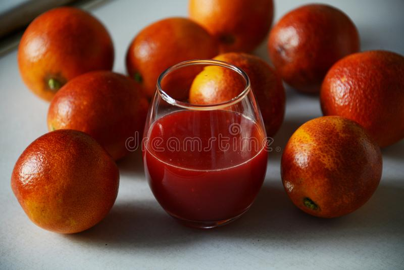 Röda Sicilian apelsiner runt om ett exponeringsglas med ny fruktsaft royaltyfri foto