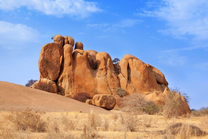 Röda skalliga granitmaxima på bakgrund för blå himmel, forntida geologiska bildande, orange stenar, naturligt gult vaggar Erongo  arkivfoton
