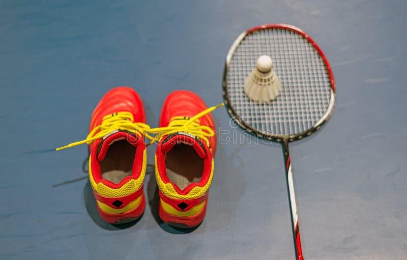 Röda skor för badminton med suddig fjäderboll och racket på domstolen arkivfoto
