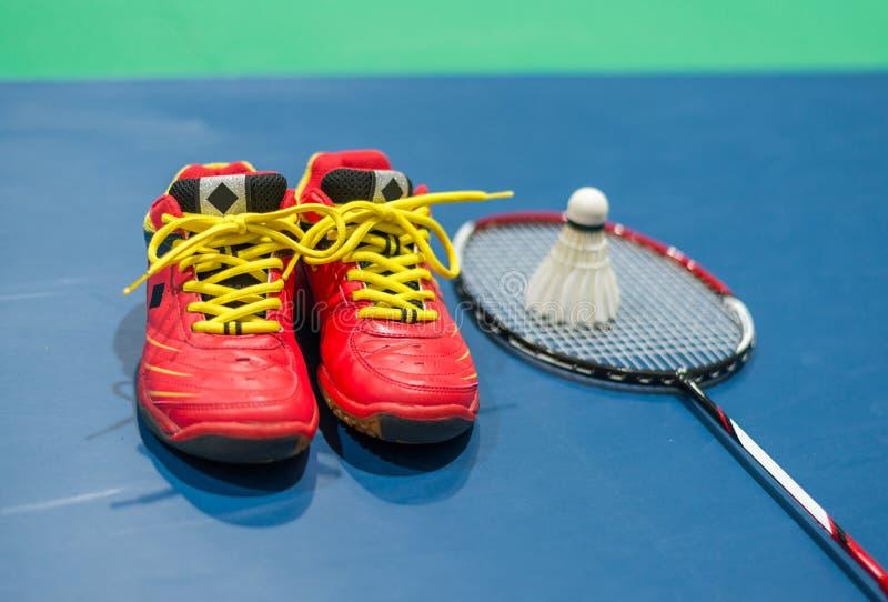 Röda skor för badminton med suddig fjäderboll och racket på domstolen arkivfoton