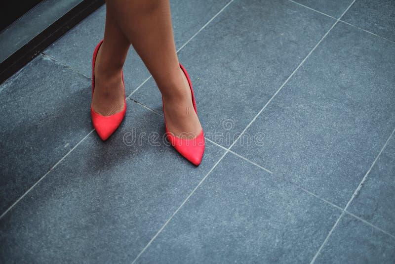 Röda skor på en kvinna` s lägger benen på ryggen arkivbild