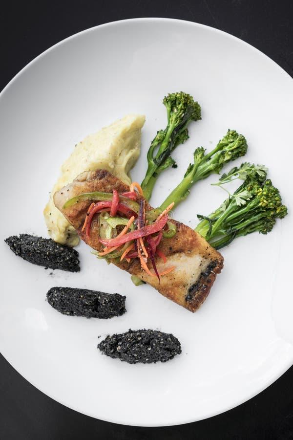 Röda snapper fiskar filén med grönsaker och svarta sesamris arkivfoton