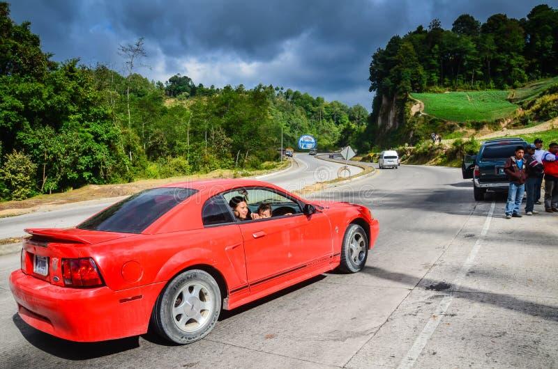 Röda Sportscar på denamerikan huvudvägen i Guatemala royaltyfria foton