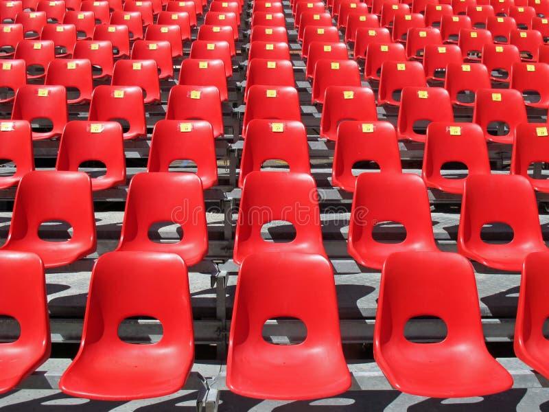 Röda stolar av den tomma stadionen royaltyfri bild