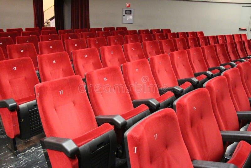 Röda stolar av teateråhörarna arkivfoto