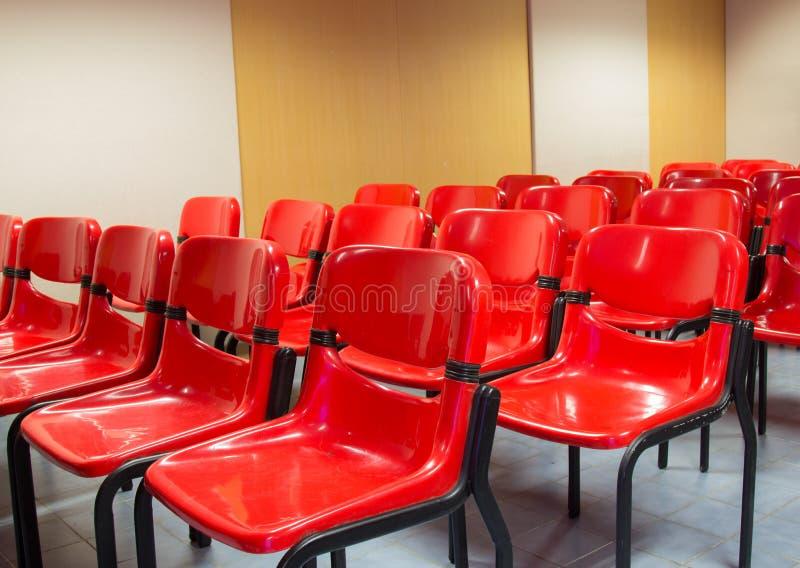 Röda stolar i mötesrummet arkivfoto