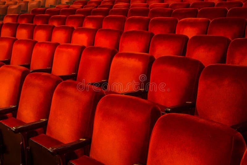 Röda stolar inom en teater arkivfoto