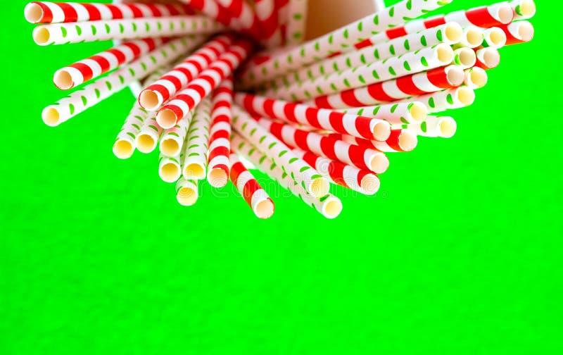 Röda sugrör för fruktsaft i en pappers- kopp på en grön bakgrund arkivbilder