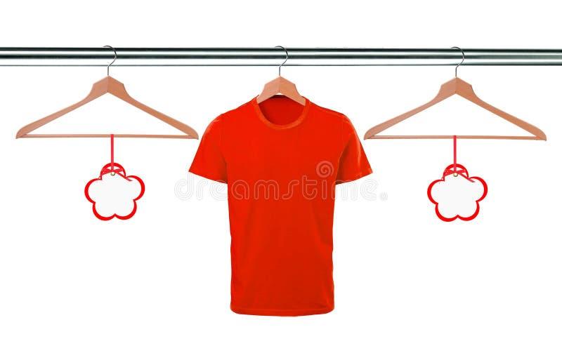 Röda t-skjortor på hängare och mellanrumsetiketter som isoleras på vit royaltyfri foto