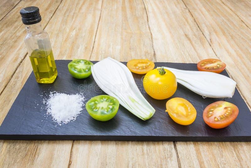 Röda tomater, guling, gräsplan, gräslökar, saltar och oljer arkivfoton