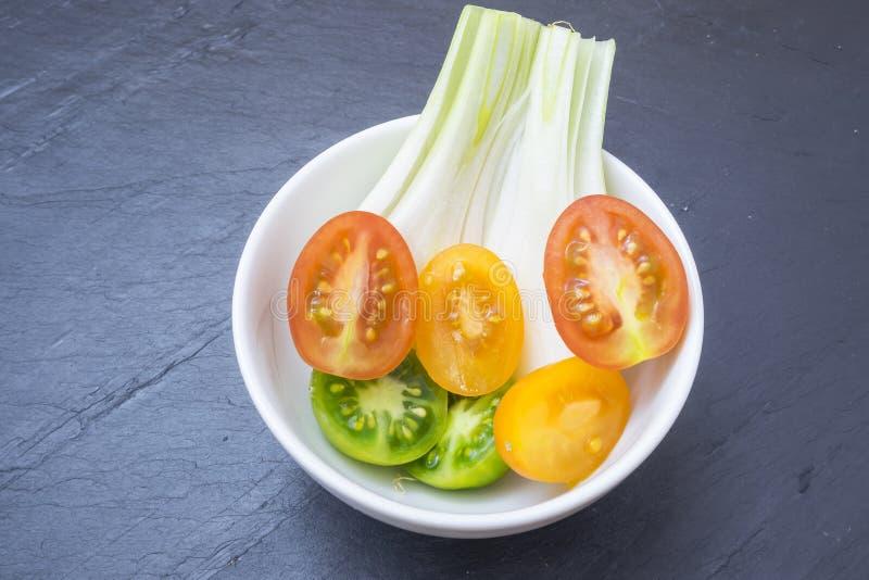 Röda tomater, guling och salladslökar fotografering för bildbyråer