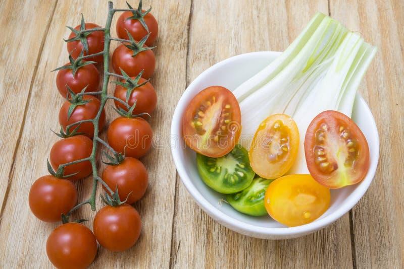 Röda tomater, guling och salladslökar royaltyfri foto