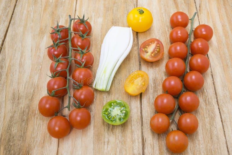 Röda tomater, guling och salladslökar royaltyfria foton