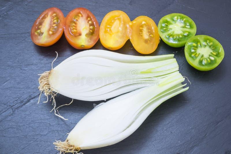 Röda tomater, guling och salladslökar arkivbilder