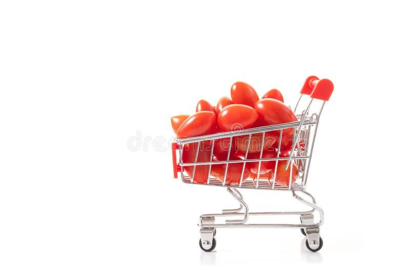 Röda tomater i shoppingvagn Sund mat för bra healt Vege arkivbild
