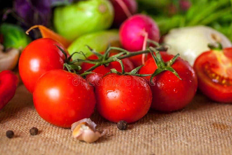 Röda tomater och mogen röd peppar med vattendroppar, sunt matbegrepp arkivfoton