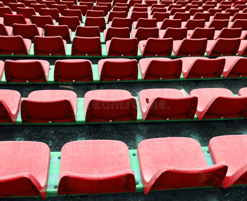 Röda tomma små stolar på stadion arkivbilder