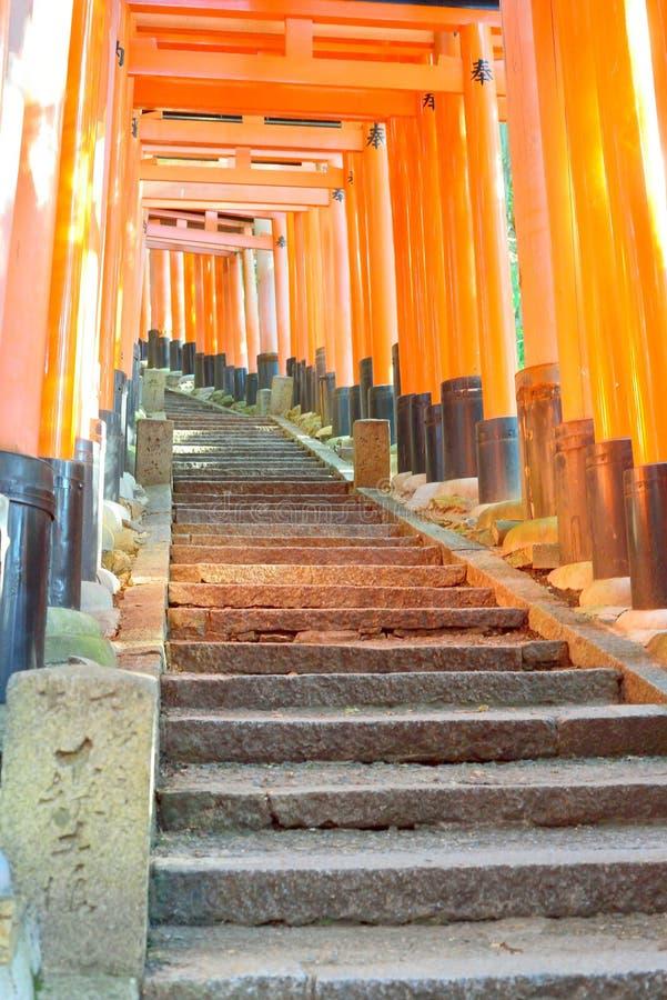 Röda toriiportar och stenmoment på Fushimi Inari förvarar, Kyoto fotografering för bildbyråer