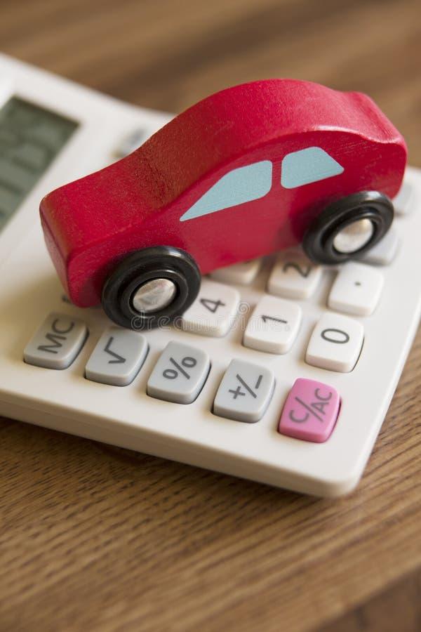 Röda Toy Wooden Car On Calculator Som Illustrerar Kostnad Av Bilism Arkivfoto