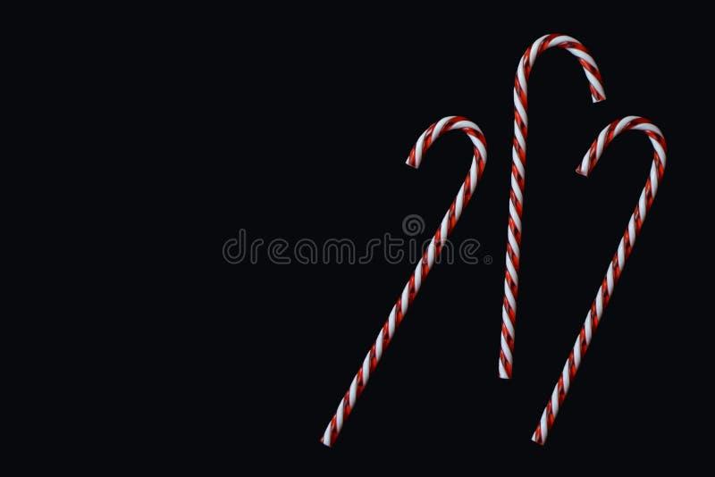 Röda tre och vita randiga traditionella julgodisrottingar på svart bakgrund arkivfoto