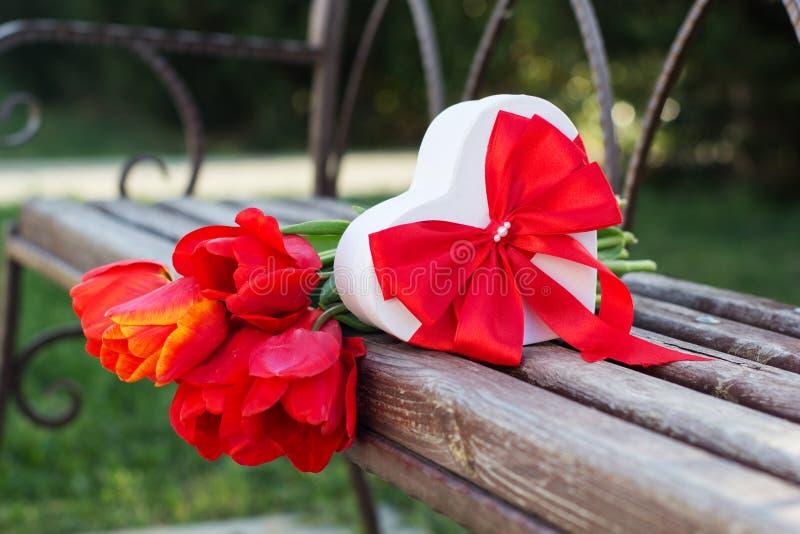 Röda tulpanblommor och gåvaask på trätabellen arkivbilder