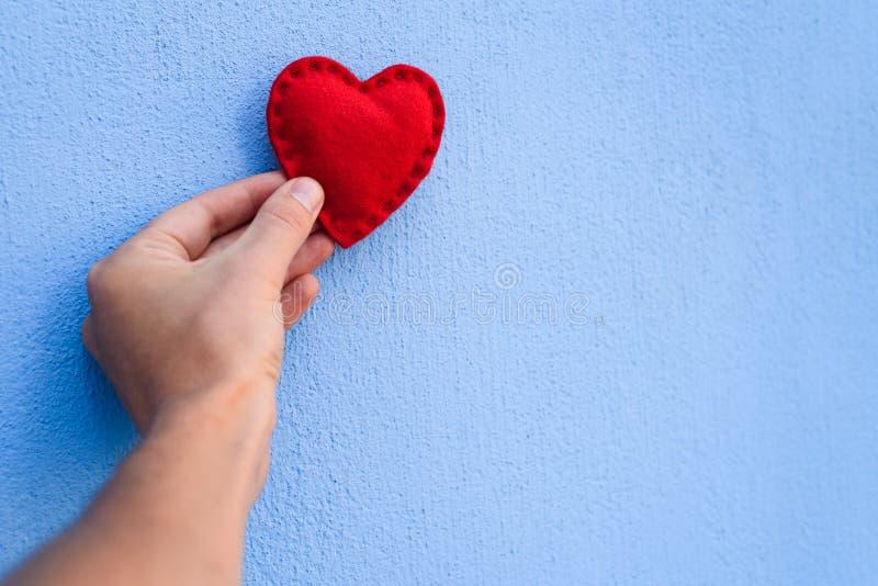 Röda valentin hjärta i handen på en blå bakgrund royaltyfri fotografi