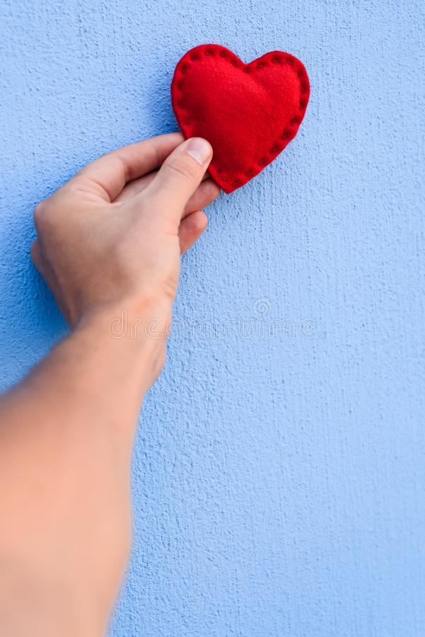 Röda valentin hjärta i handen på en blå bakgrund royaltyfria bilder
