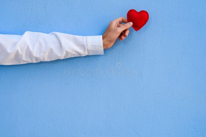 Röda valentin hjärta i handen på en blå bakgrund arkivbild