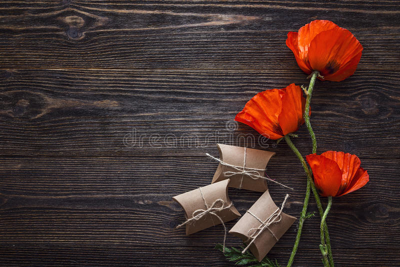 Röda vallmo blommar med gåvaaskar på mörk wood bakgrund arkivfoto