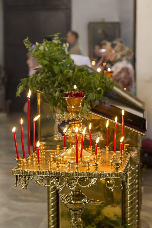 Röda vaxstearinljus på en ljusstake i den ortodoxa kyrkan royaltyfri foto