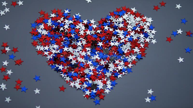 Röda vita blåa skinande konfettistjärnor på grå bakgrund, den tricolor begrepps-, självständighet- och frihetsdagen USA royaltyfri fotografi