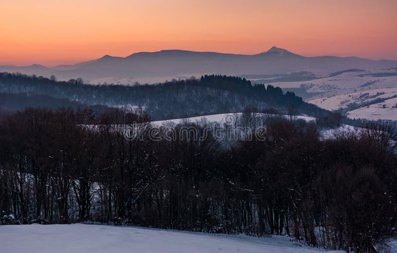 Rödaktig vinterskymning i berg med det höga maximumet fotografering för bildbyråer