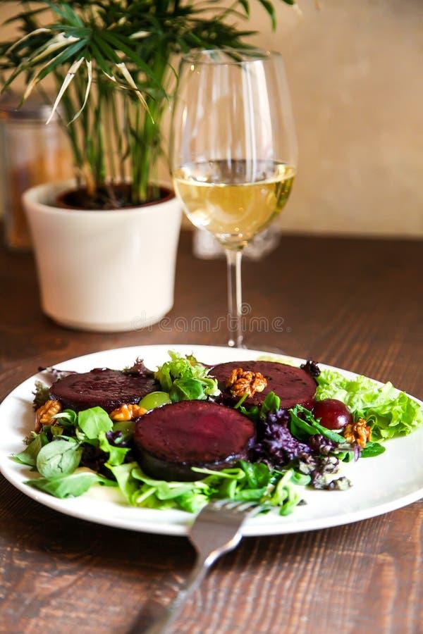 Rödbetabiffsallad med ädelostsås, druvor och valnötter arkivbild
